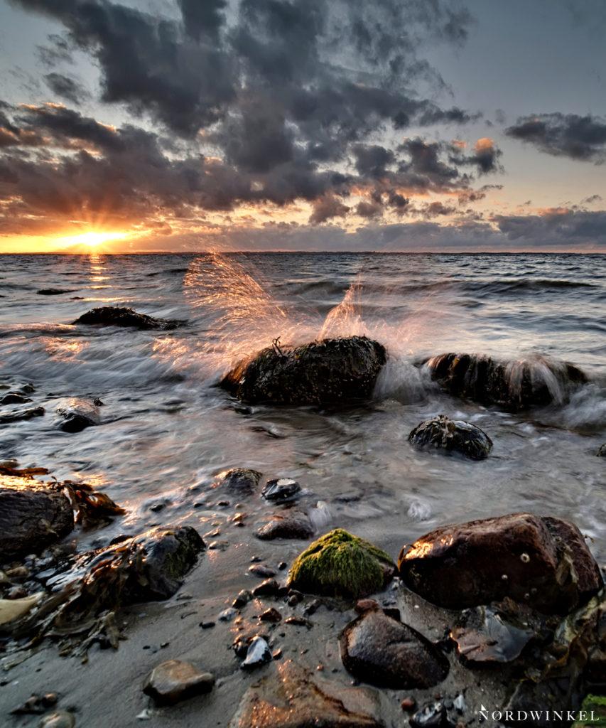 rauschende welle bricht zum sonnenuntergang an der ostsee über steine