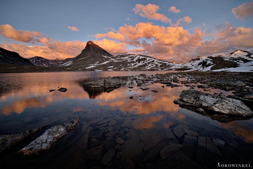 orange wolken über bergkulisse hinter einem see