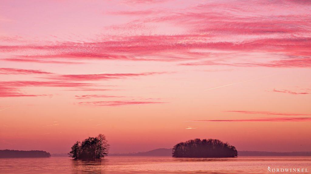 roter abendhimmel über einem see mit zwei inseln willst du ernsthaft fotografieren lernen bekommst du bald solche bilder hin