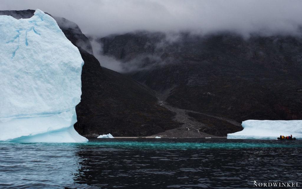 riesiger eisberg neben einem kleinen schlauchboot