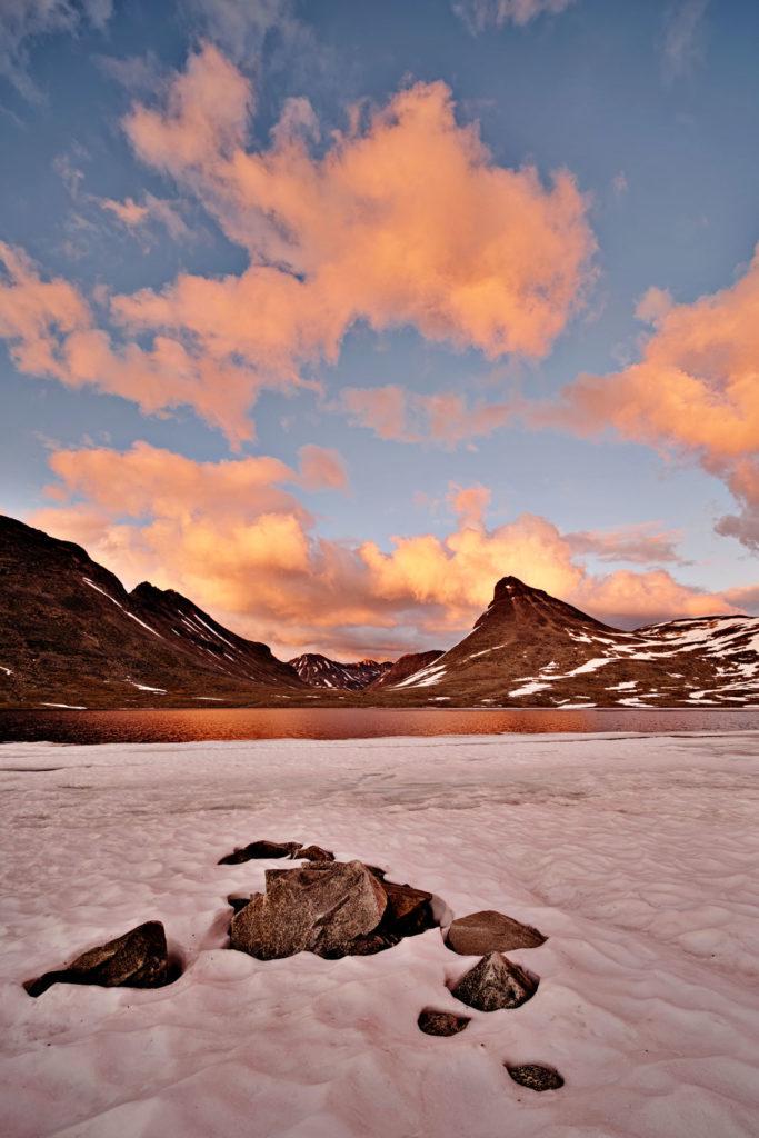 zugefrorener see im gebirge unter orangenen wolken