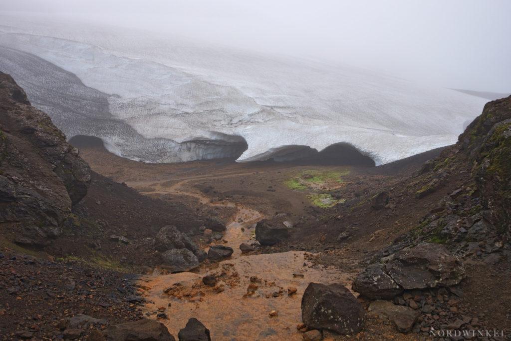 schneedecke unter Nebel auf felsig-morastigem Untergrund