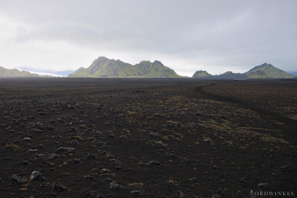 Laufen über ein riesiges Vulkanaschefeld aus dem moosige Berge ragen