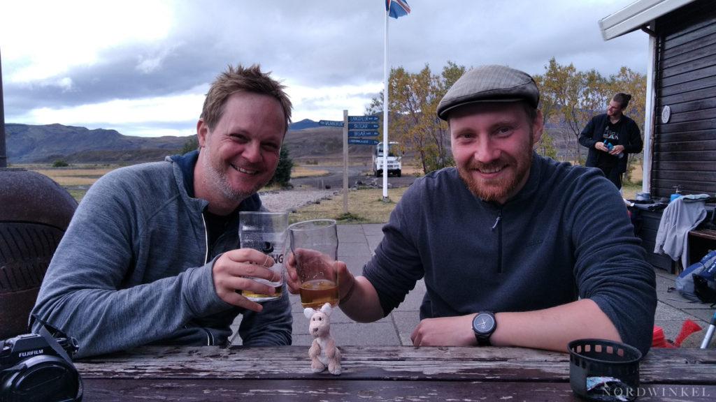 Oleg und Konrad sitzen am Tisch in Thorsmörk und stoßen auf die Wanderung an