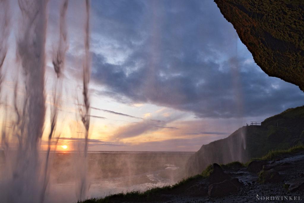 Blick über einen Abendhimmel durch die Kaskaden des Seljalandsfoss