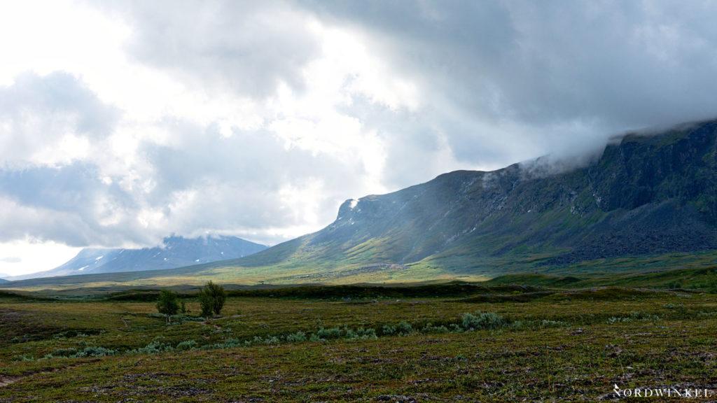 das Ákká-Massiv unter Wolken davor eine grüne Landschaft aus arktischer Tundra
